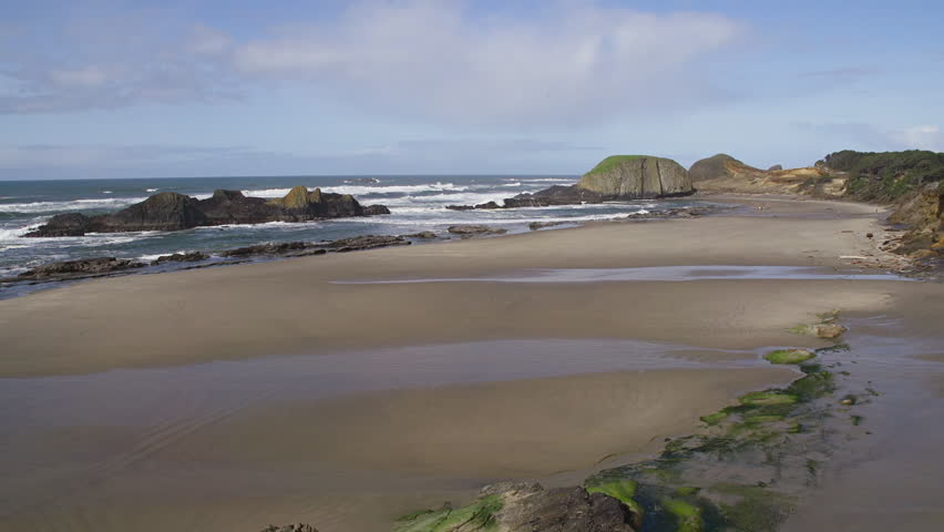 Pacific Ocean tides flow gently against rocks and sand on Seal Rock Beach near