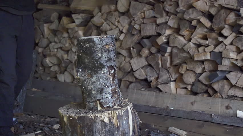 Man splits a length of spruce firewood with an ax in a wilderness wood shed in
