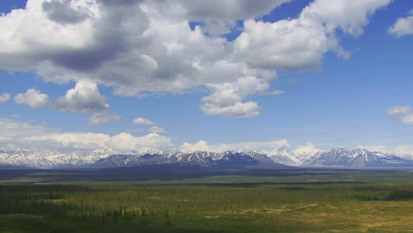 Slow time lapse of scenic Alaskan interior tundra prairie dotted with lakes and snow-capped mountain glaciers beyond