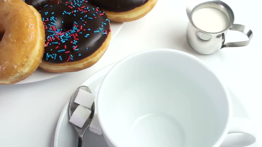 1920x1080 Coffee poured to wash down glazed, chocolate donuts with sprinkles.