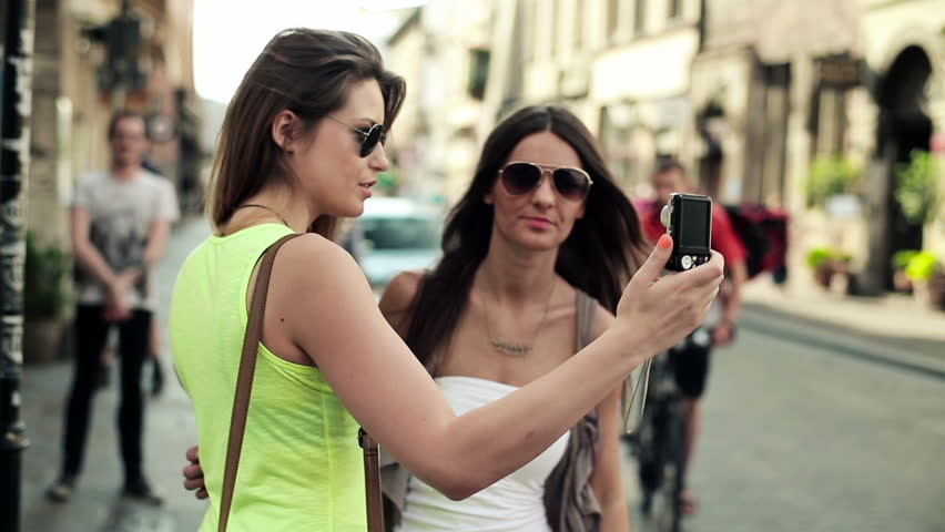 Tourists, girlfriends taking photo with photo camera in city