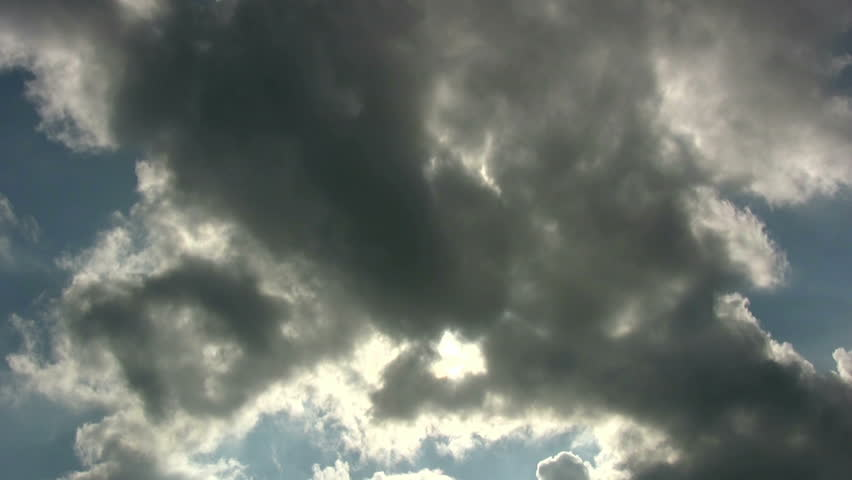 Time lapse of dark, moving clouds on a blue sky sky with penetrating sun.