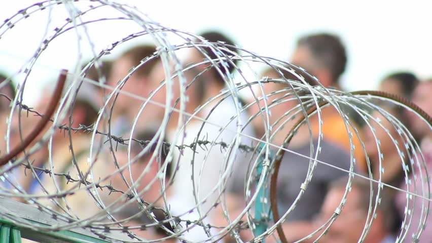 Barbed wire with people on background