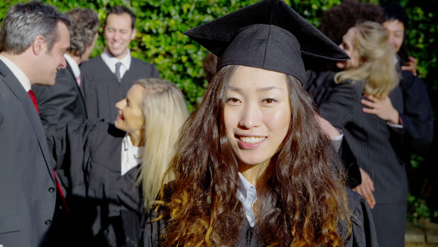 Portrait of a happy female graduate on graduation day. She smiles at the camera as her friends and their families celebrate behind her. In slow motion.