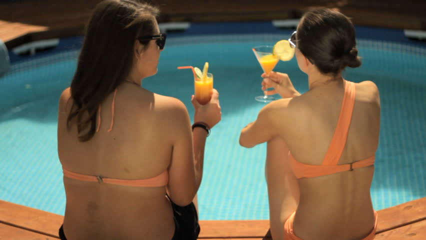 Pretty girls drinking by the pool