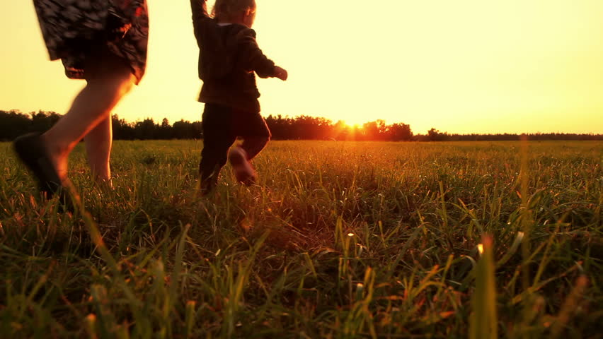 Mother and baby are running across the field at sunset (dolly shot)