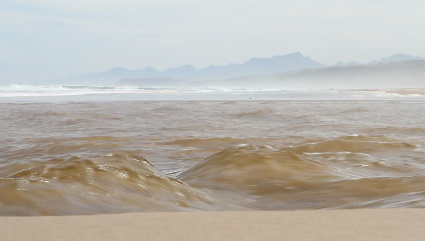 River flows into the ocean as the tide changes