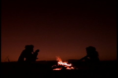 Historical reenactment in East Africa. Silhouettes of family of early humans, or Homo erectus, sitting around a camp fire.