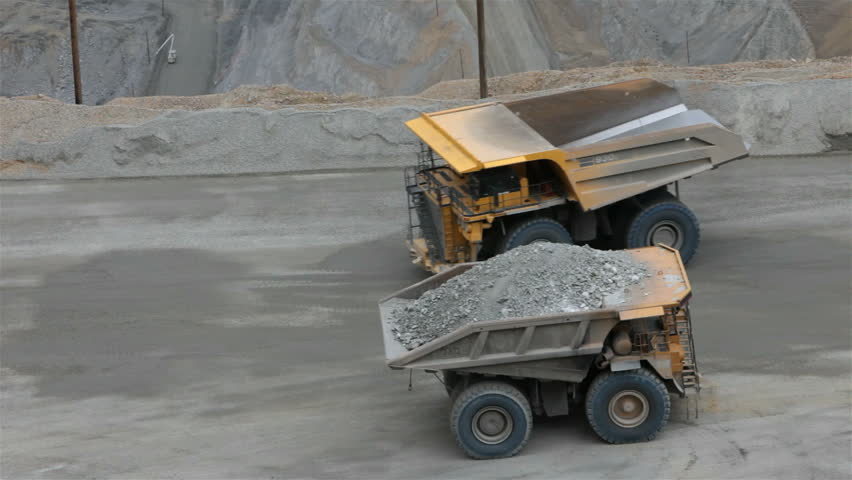 Two large dump trucks passing Kennecott Copper Mine central Utah. Open pit. Worlds largest open pit copper mine.  Ophir Mountains Salt Lake City. Tons of rock and minerals driving slow on dirt road.