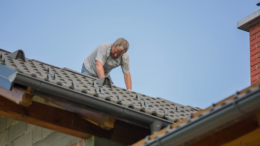 Man Adding New Top Roof Tile. Destroyed roof tiles on completely new house with no facade and no insurance yet. Man changes broken tiles because of hail storm destroyed the roof.