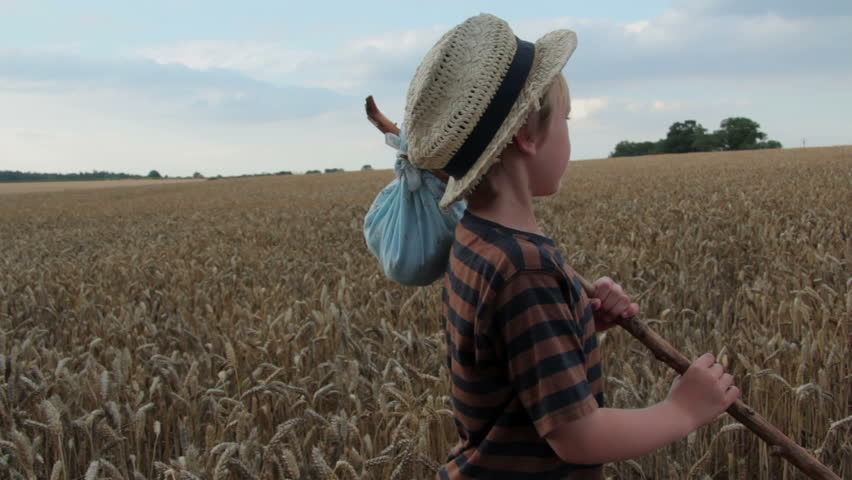 A young boy wanders through a corn field with all he owns wrapped in an old bandana hanging on a stick. Is he a modern Tom Sawyer or Huckleberry Finn?