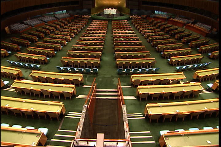 NEW YORK CITY - FEBRUARY 11, 1999: Wide angle of rows of seats in general assembly, camera tilts up to WS of the United Nations General Assembly hall