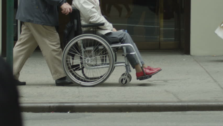 Low angle view of an elderly lady in a wheelchair being pushed along a crowded city street. In slow motion.
