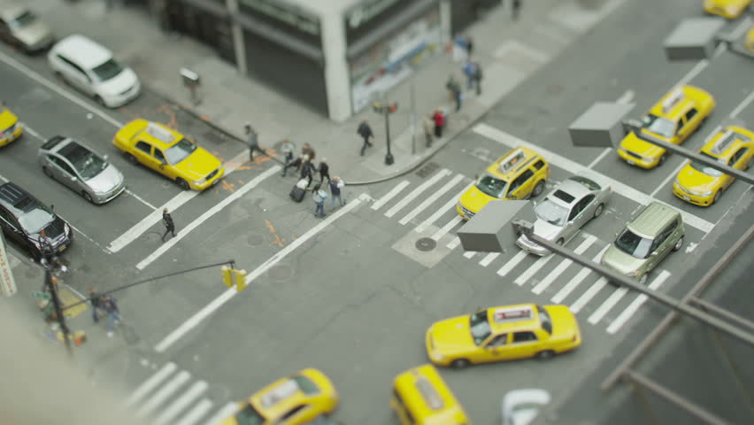 Overhead view of yellow cabs and other traffic at a busy New York intersection. In slow motion.