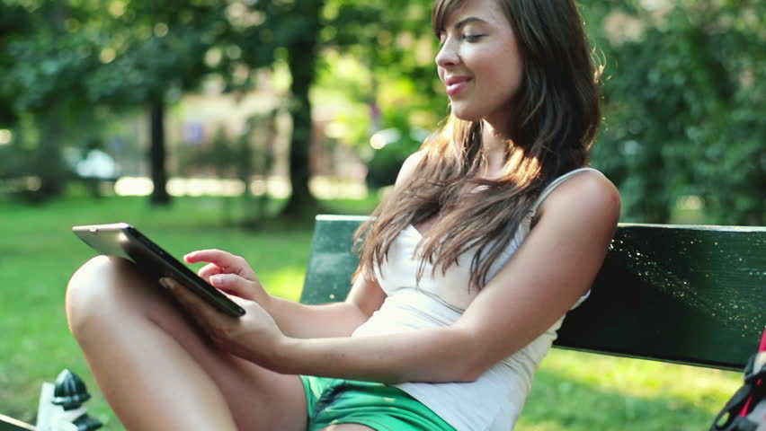 Cute young woman with tablet in the park, steadicam shot