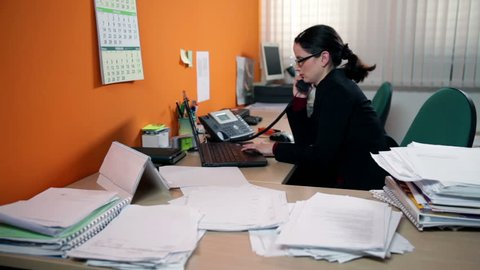 Business woman in office behind computer making a call