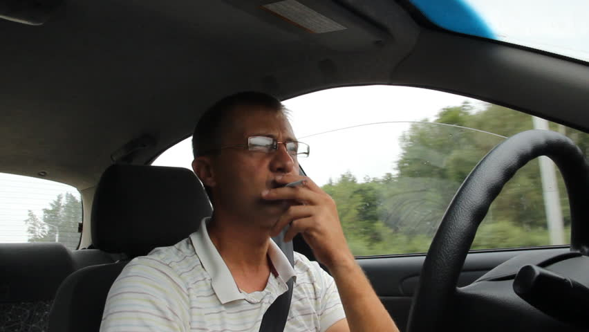 A man with a cigarette behind the wheel of a car     Shutterstock HD Video #4455569