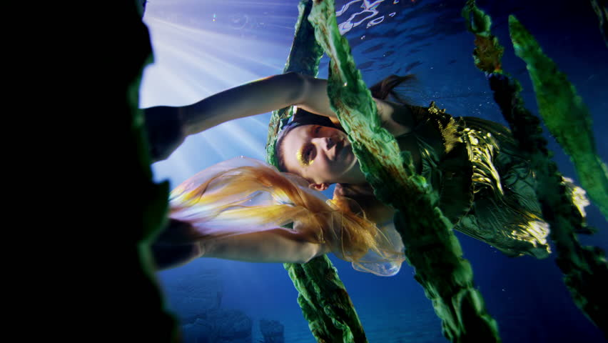 Beautiful mysterious woman with flowing blonde hair and gold dress. She is swimming amongst the seaweed in a vibrant underwater environment, with rays of light penetrating the depths.