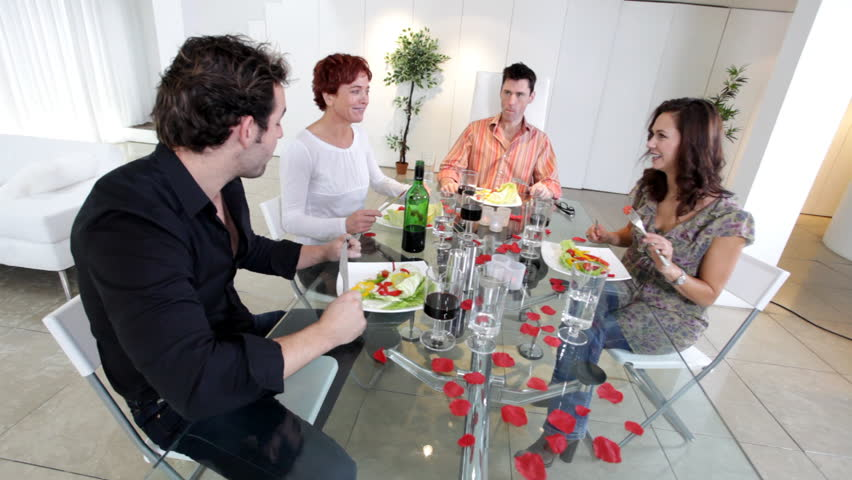 Group of family or friends with nice lifestyle sit down for a dinner party in their contemporary home.