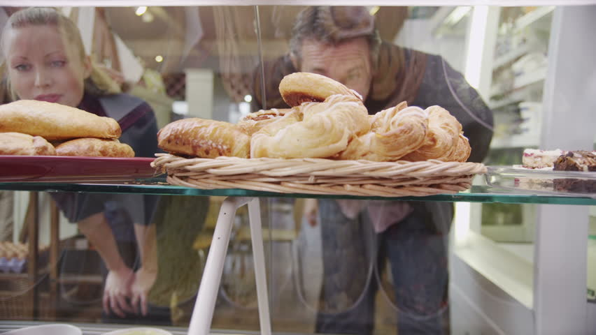 Happy customers looking through the glass and choosing fresh pastries at the bakery counter. In slow motion.   Shutterstock HD Video #4506611