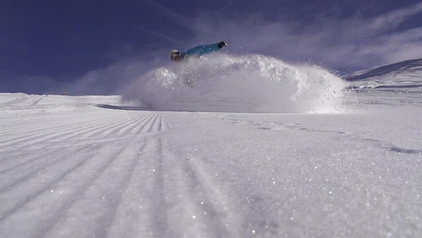 SLOW MOTION: Snowboarder spraying snow into camera