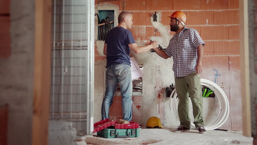 People and teamwork, team of two men at work in construction site, manual workers saluting and collaborating. Part 4 of 11   Shutterstock HD Video #4522199