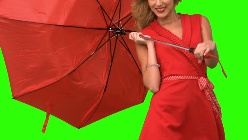 Woman in high heels holding a broken umbrella on green screen in slow motion