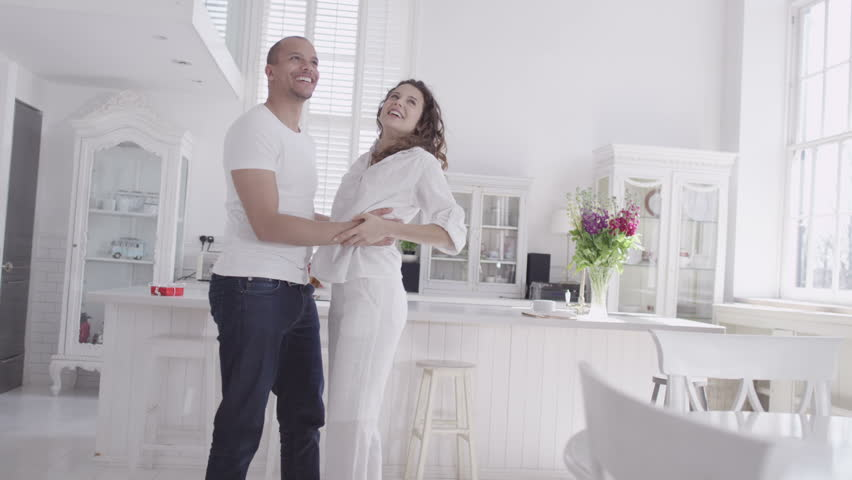 Happy and attractive young mixed race couple viewing a beautiful modern property with a view to making it their home. In slow motion. | Shutterstock HD Video #4531829