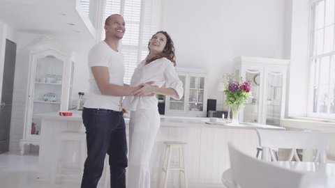 Happy and attractive young mixed race couple viewing a beautiful modern property with a view to making it their home. In slow motion.