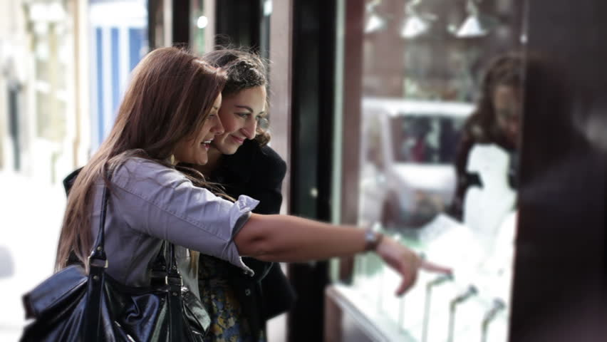 Young friends or students looking at cute clothes or jewelry in a shop window