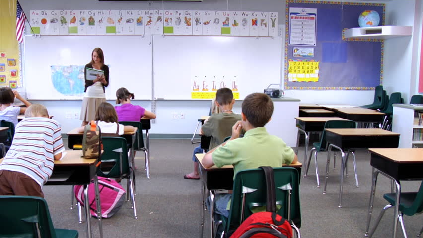 Elementary Classroom Pictures : Student standing up in front of class reading paper stock