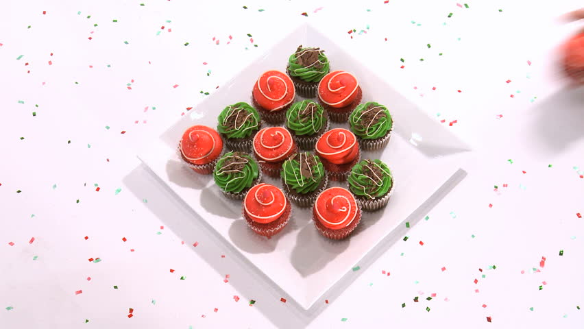 A square plate of 16 red and green cupcakes gradually empties itself as guests serve themselves. Ideal to illustrate parties, christmas, abundance or gluttony.