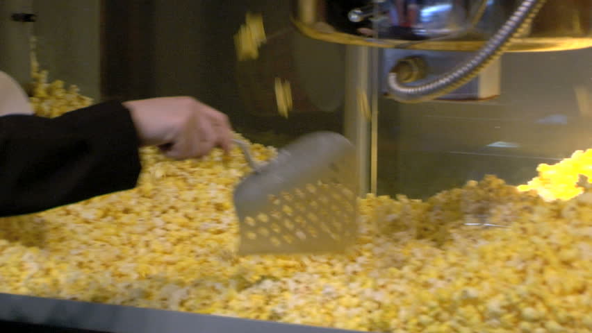 An employee from a movie theater fills up a bucket of fresh popcorn.