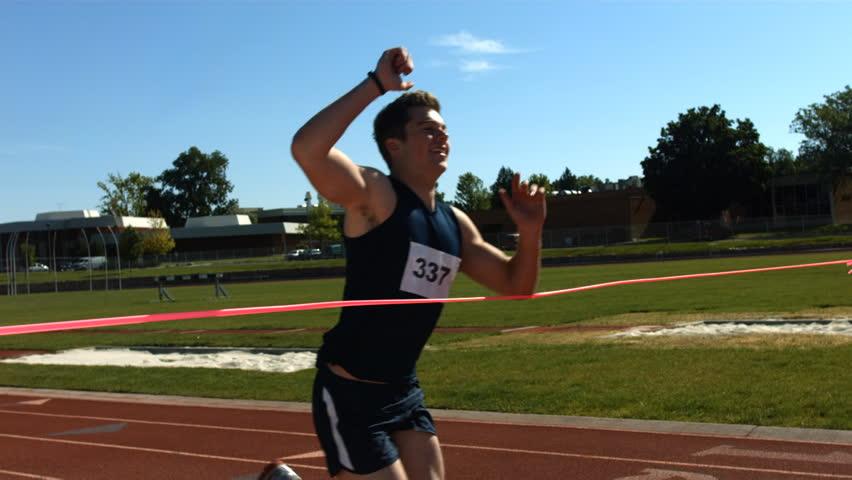 Track runner crosses finish line, slow motion