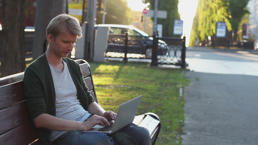 Young adult man works on laptop smiles, business success, author