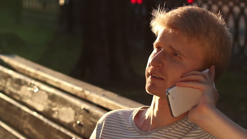 Talking over phone outdoors young male makes a call happy man