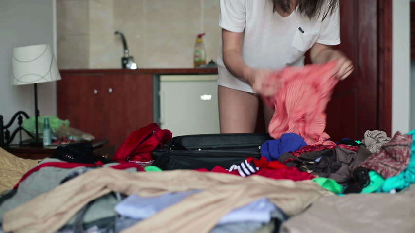 Woman hands packing suitcase