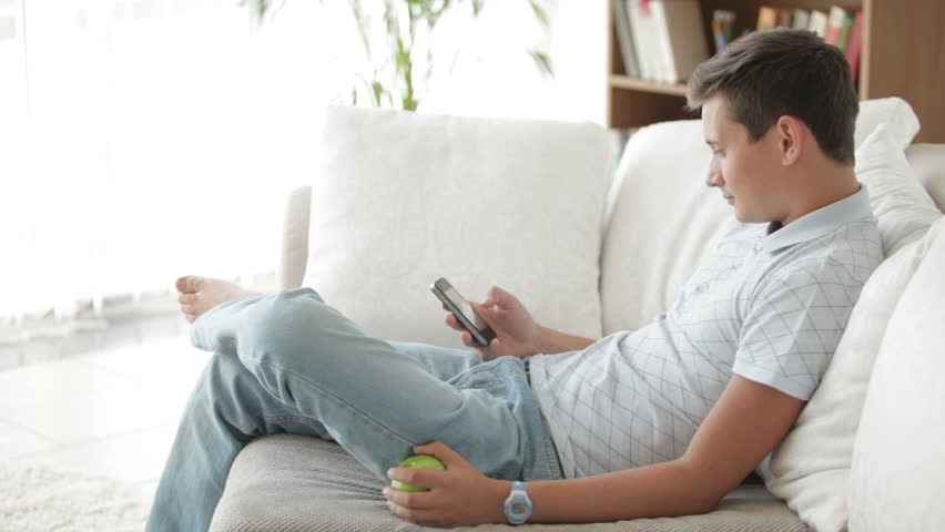 Cheerful guy sitting on sofa using mobile phone and for Bequeme couch