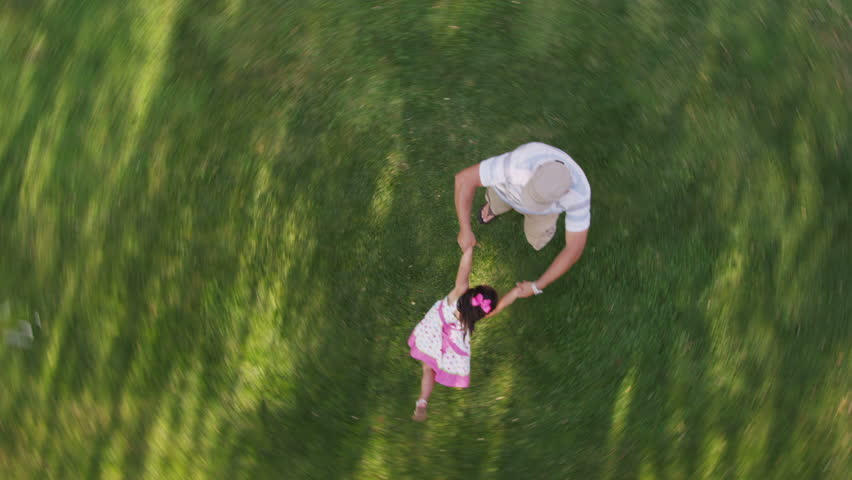 Overhead shot of father spinning around with daughter in yard