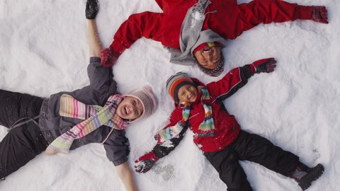 Family laying in winter snow, overhead shot