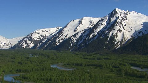 Aerial shot of forest streams and snowy mountains, Alaska