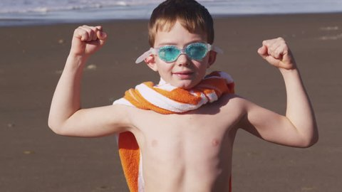 Young boy at beach flexing muscles with superhero costume