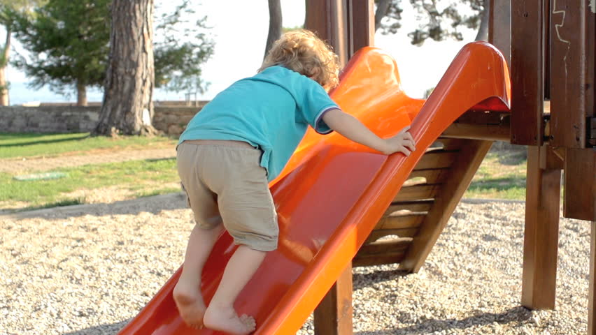 Slow Motion Shot Of A Little Red-Haired Boy Climbing Up A Slide Outdoors In The