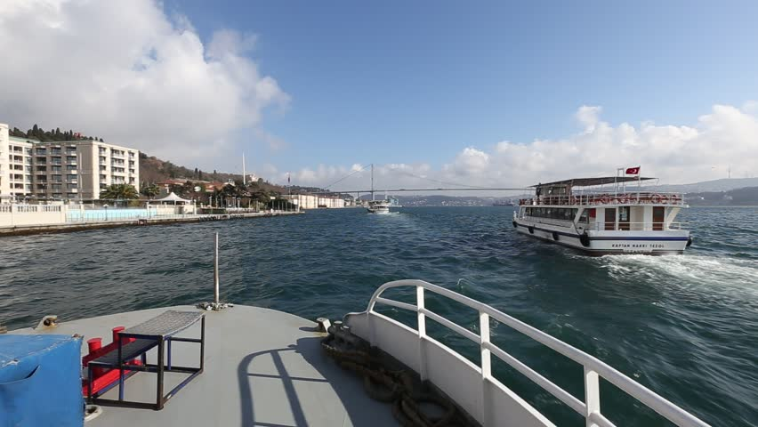 ISTANBUL, TURKEY - FEB 1: Tourist boats cruise to the Bosphorus Bridge (Ataturk Bridge) on Feb 1, 2013 in Istanbul, Turkey. Ataturk Bridge is a first suspension bridge over the Bosphorus Strait.