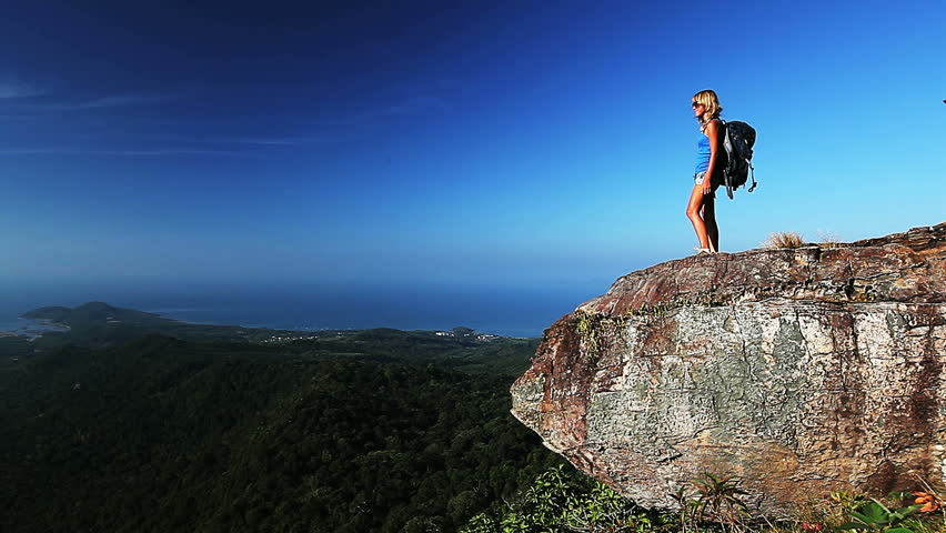 Young Lady Hiker With Backpack Reaching Top Of A Mountain