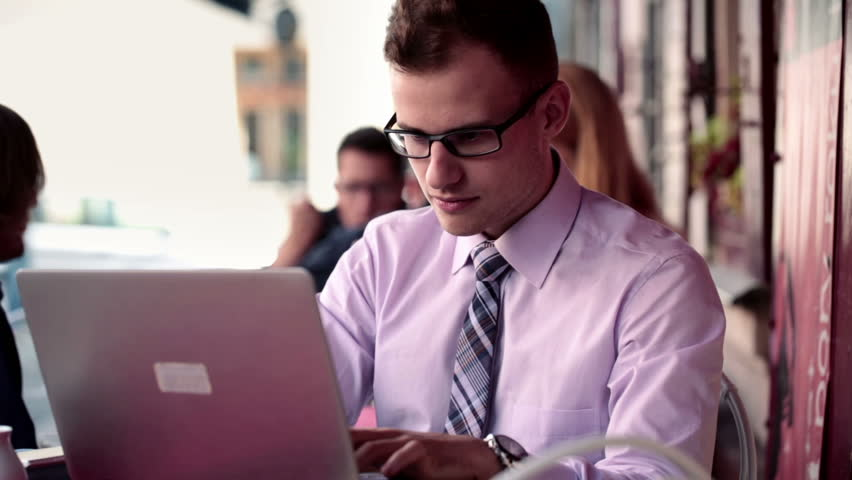 Successful happy businessman with laptop computer in cafe