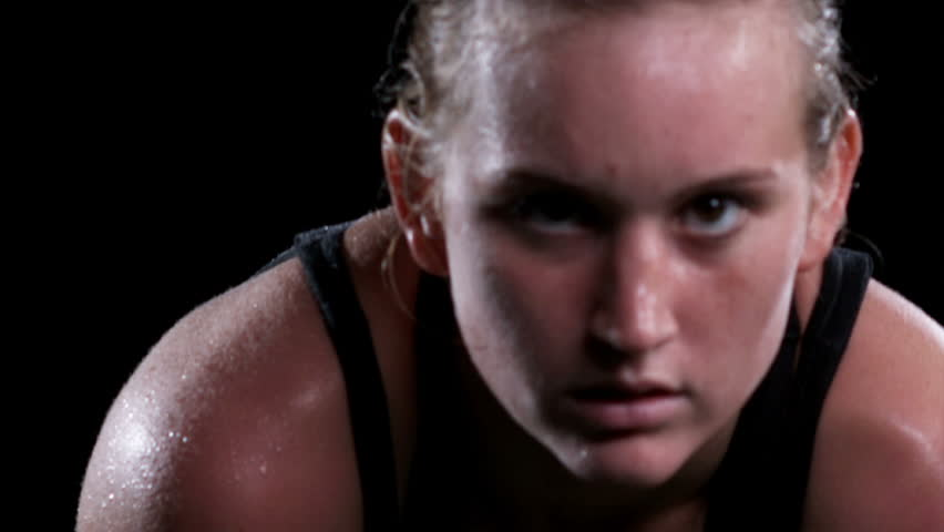 A female athlete breathes heavy and sweats after an intense exercise while looking into the camera in a dark gym, close up portrait