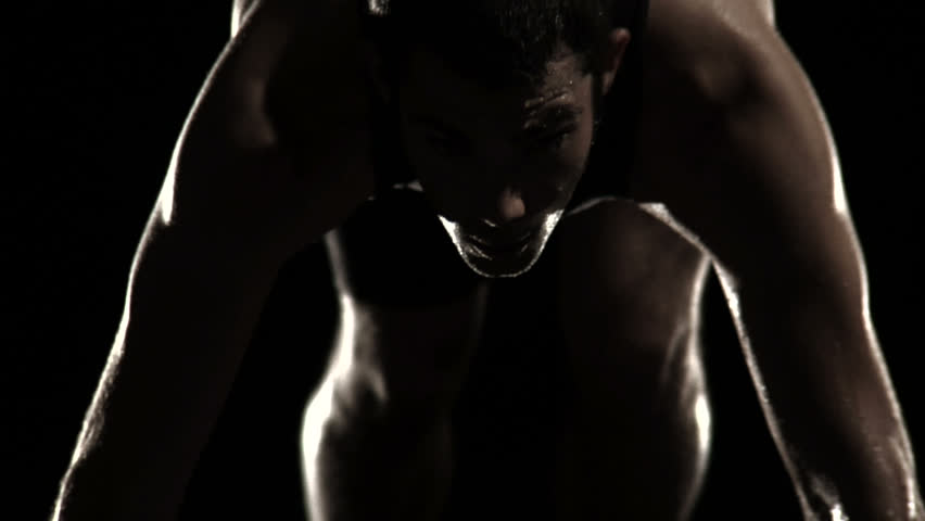 A male athlete runner gets himself set at the starting line of a track ready to sprint in the shadows