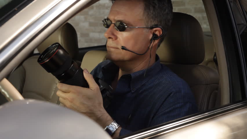 An undercover agent puts down his camera and speaks into a small earpiece he is wearing.