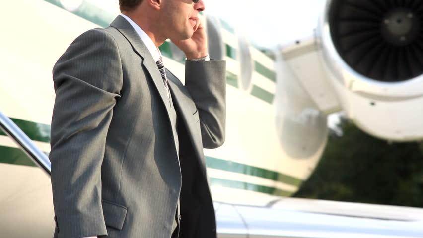 Businessman walks off jet talking on cell phone